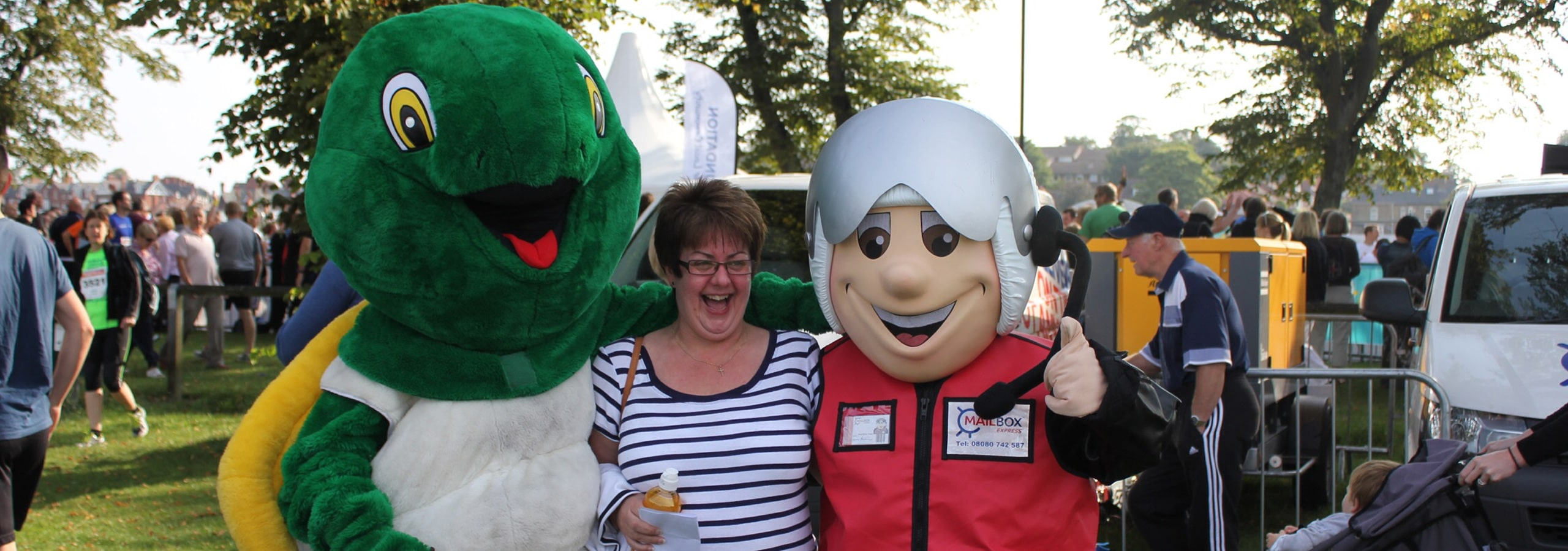 Lady flanked by Mailbox Express mascot and giant furry turtle
