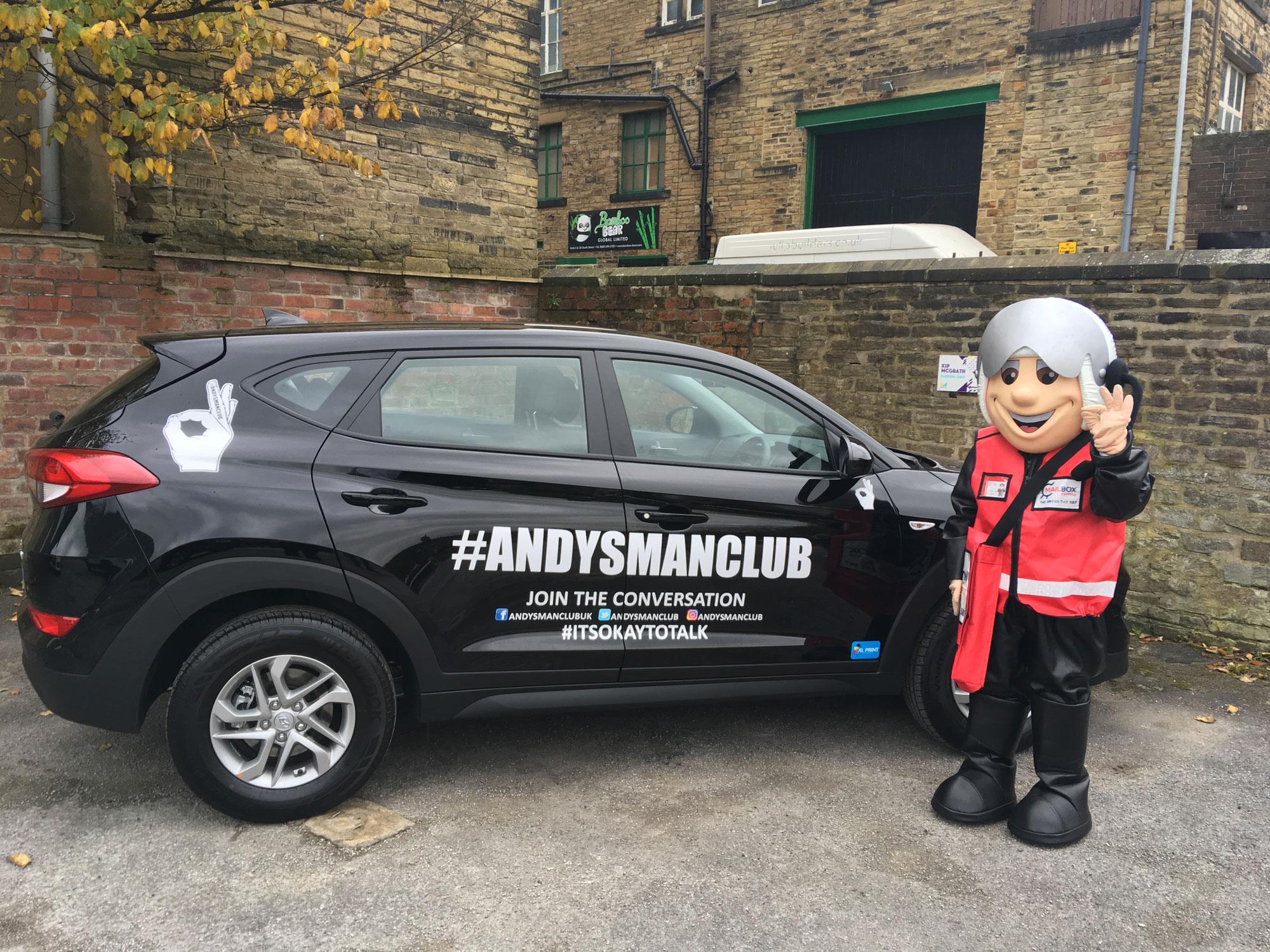 Black car with andysmanclub hashtag next to Mailbox mascot