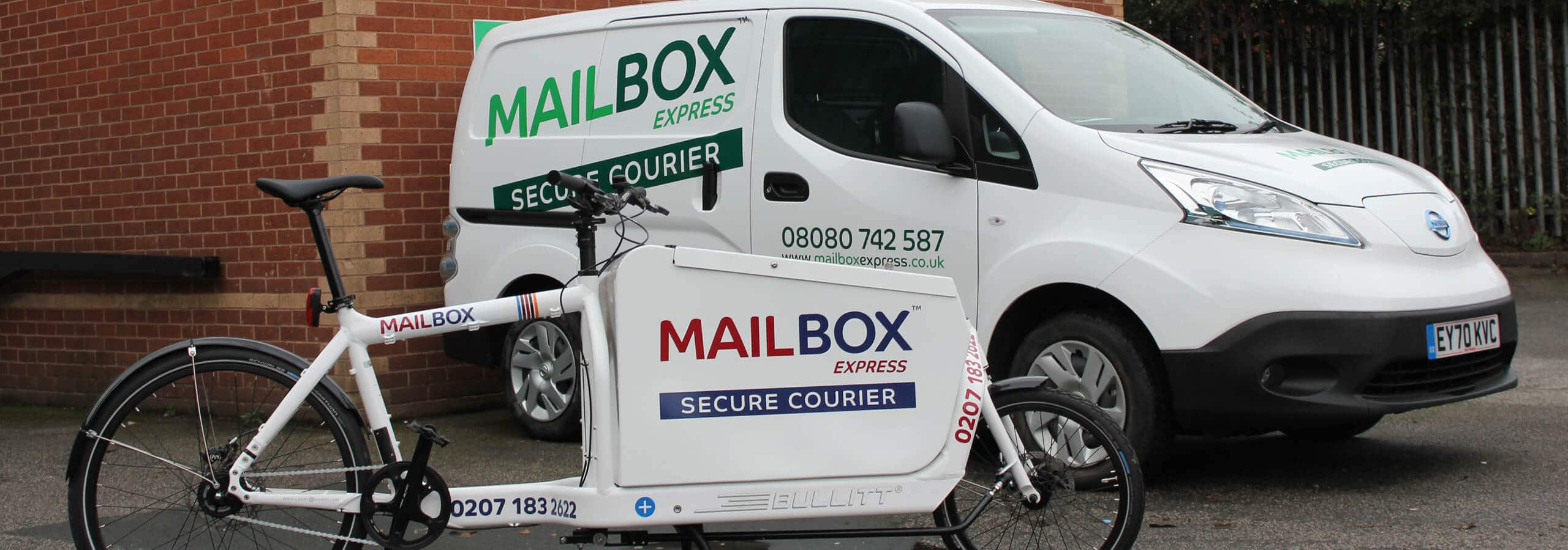 Mailbox branded van and push bike outside Mailbox building